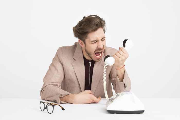 man wearing brown suit jacket mocking on white telephone